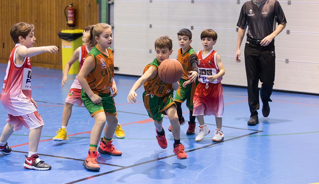 """L'Àlex Valiente puja la pilota al partit contra el Pineda. El nostre Premini """"B"""" mixt estrena la publicitat de Kids&Us. Foto: Joan Maria Arenaza"""